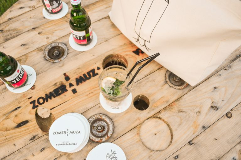 Variation of Bar Muza's logo for summer concept Zomer Bar Muza, as a brand mark on a wooden table.