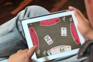A man plays a digital card game on an Ipad.