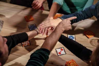 People cross hands while playing a Cartamundi card game.