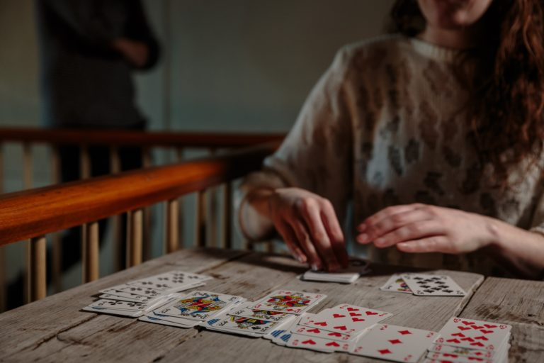 A woman plays Patience with a deck of Cartamundi playing cards.