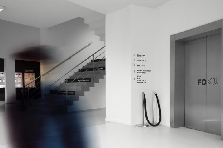 Museum signage in FOMU's visual identity and FOMU logo on elevator doors.