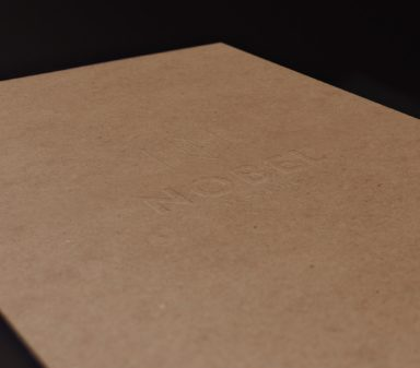 Nobel logotype embossed on cardboard map.