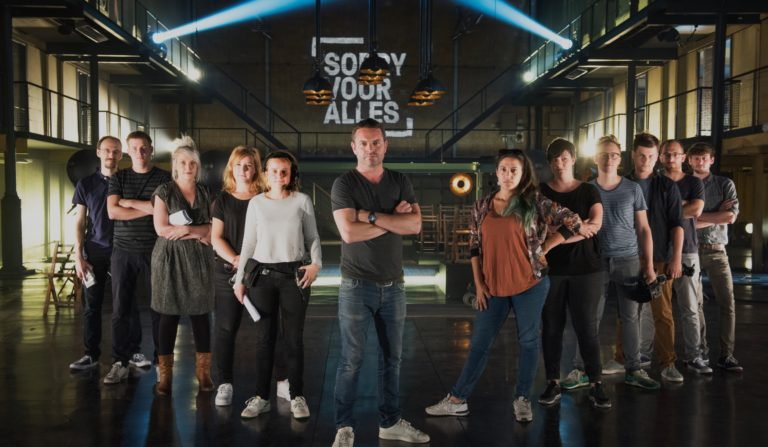 Sorry Voor Alles' cast and crew posing in front of a wall projection of the TV show's new logo.