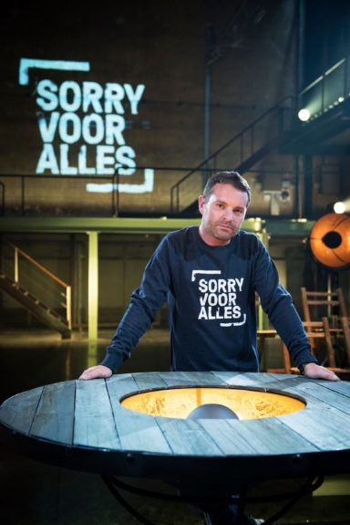 Sorry Voor Alles logo used as a wall projection and on a sweatshirt.